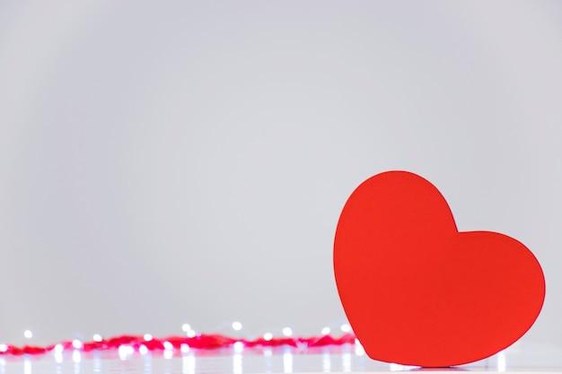 Puste pudełko z czerwonym sercem z wolnym miejscem na tekst lub emblemat z podświetleniem bokeh na szaro