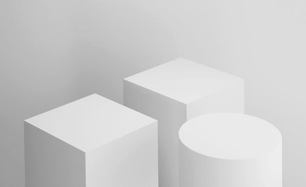 Puste pudełkowe kostki na podium z cylindrem na białym szarym