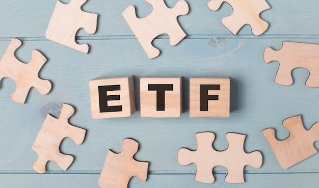 Puste puzzle i drewniane kostki z etf exchange traded funds leżą na jasnoniebieskim tle.