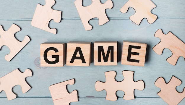 Puste puzzle i drewniane kostki z grą leżą na jasnoniebieskim tle.