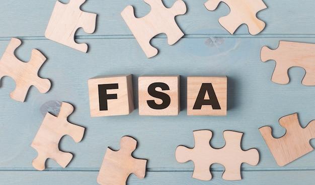 Puste puzzle i drewniane kostki z kontem fsa flexible spending account leżą na jasnoniebieskim tle.