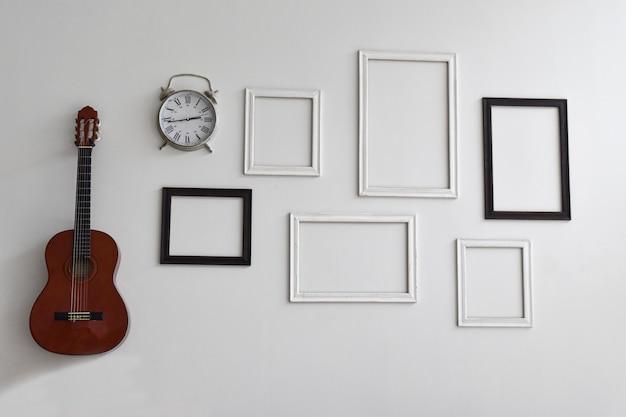 Puste ramki do zdjęć, zegar i gitara na ścianie z białego cementu.