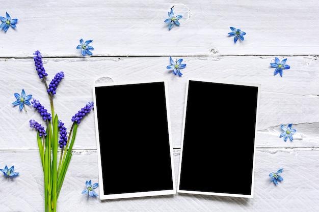 Puste ramki na zdjęcia i bukiet wiosennych kwiatów niebieski
