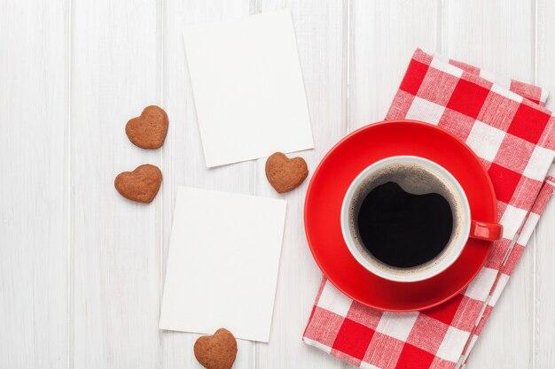 Puste ramki na zdjęcia walentynkowe, filiżanka kawy i ciasteczka w kształcie serca na białym drewnianym stole
