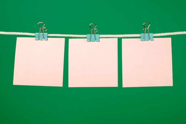 Puste różowe kartki papieru wiszące na sznurku