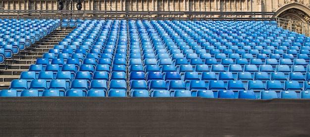 Puste rzędy krzeseł, siedzenia w sali koncertowej, w sali sportowej.