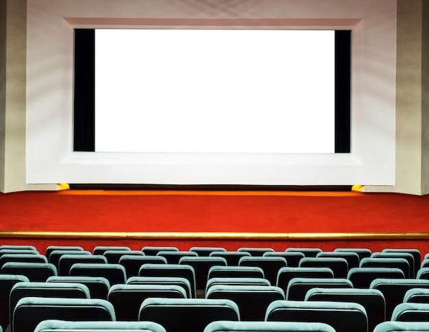 Puste rzędy wygodnych siedzeń z dużym ekranem w kinie.