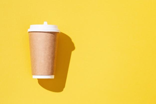 Puste rzemiosło zabiera duży papierowy kubek do pakowania kawy lub napojów na żółtym tle
