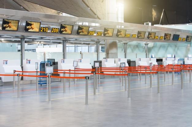 Puste ścieżki ograniczone czerwoną wstążką do stanowisk odprawy i odprawy bagażu w terminalu pasażerskim.