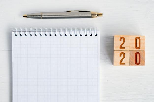 Puste spiralny notatnik, wieczne pióro, drewniane kostki z numerami nowy rok