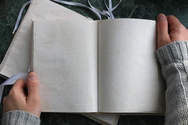 Puste strony otwarte rocznika książki na zielonym marmurowym blacie