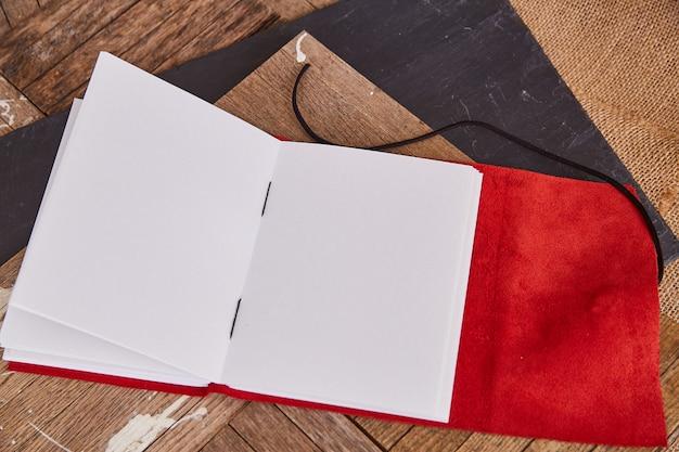 Puste strony otwartej książki z czerwoną skórą na starym drewnie
