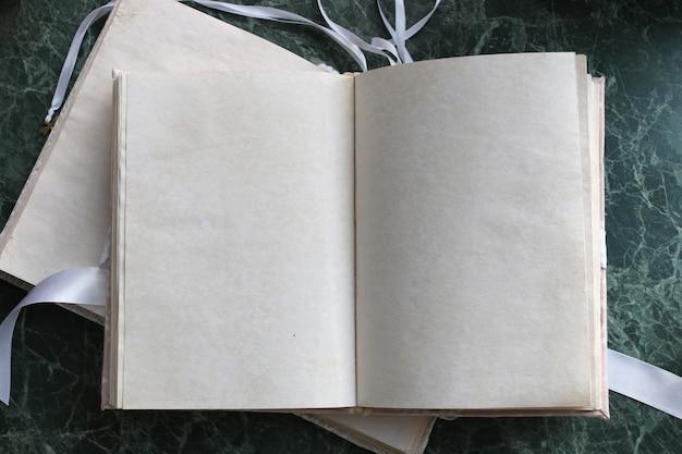 Puste strony otworzyły starą książkę na zielonym marmurowym blacie