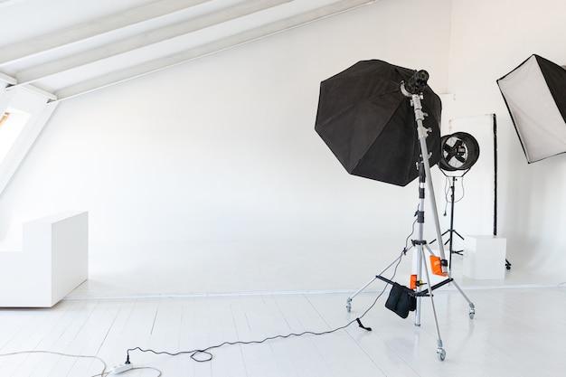 Puste studio fotograficzne ze sprzętem oświetleniowym. lampa błyskowa, sceny gotowe do fotografowania