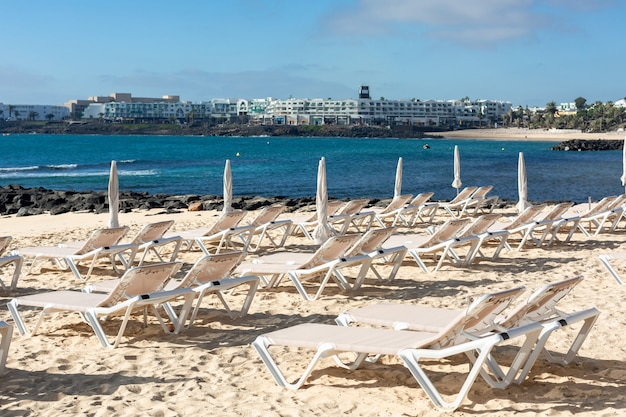 Puste Szezlongi Na Plaży W Mieście Costa Teguise. Wyspa Lanzarote, Hiszpania. Premium Zdjęcia