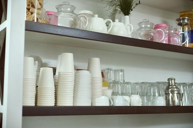 Puste szklanki, filiżanki, czajniki i patelnie do spawania na drewnianej półce baru