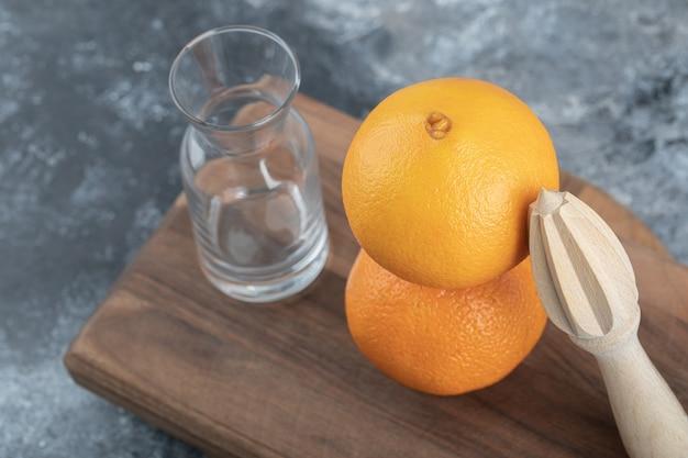 Puste szklanki i pomarańcza na desce.