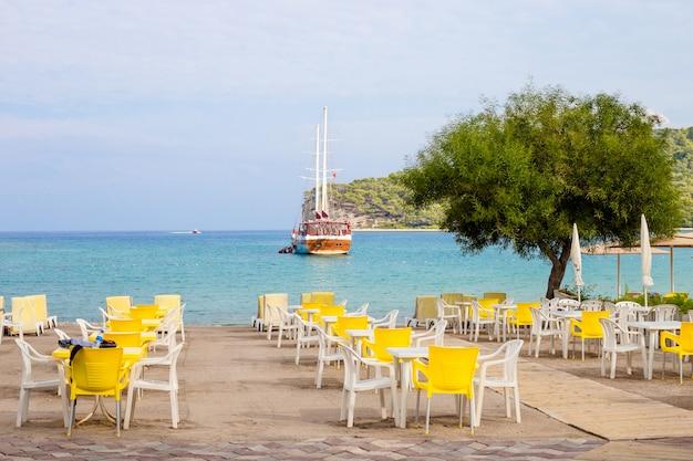 Puste tabele kawiarni na plaży kemer, turcja.