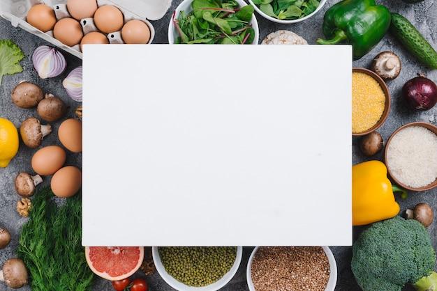 Puste tabliczki nad kolorowymi warzywami; jajka; owoce i rośliny strączkowe