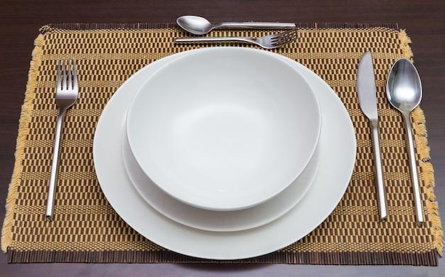 Puste talerze obiadowe wihte i naczynia na ciemny drewniany stół