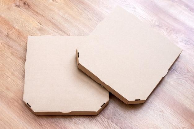 Puste tektury do pizzy. zabierz brązowe pudełka po pizzy na drewnianym tle. widok z przodu opakowania na żywność.