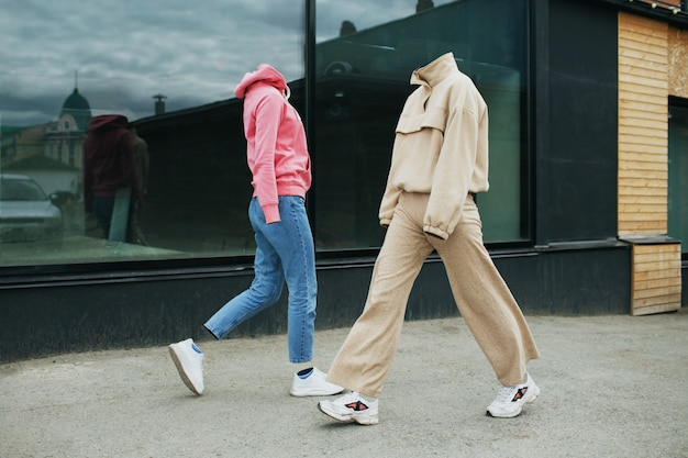 Puste ubrania kobiety chodzą po ulicy w bluzie z kapturem, spodniach dżinsowych, tenisówkach i kolorowych trampkach.