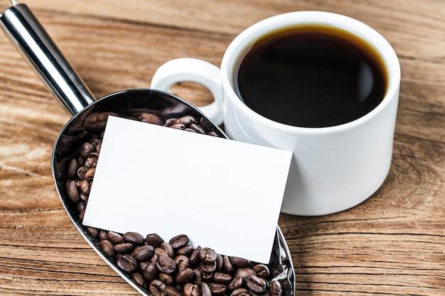 Puste wizytówki i filiżankę kawy na drewnianym stole. korporacyjne marki stacjonarne makijaż.