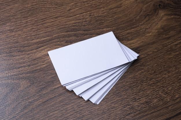 Puste wizytówki na drewnianej ścianie. papier firmowy, biurko kreatywnego projektanta. leżał na płasko. skopiuj miejsce na tekst.