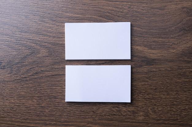 Puste wizytówki na podłoże drewniane. papeteria firmowa, makiety brandingu. kreatywne biurko projektanta. leżał na płasko. skopiuj miejsce na tekst. szablon identyfikatora.