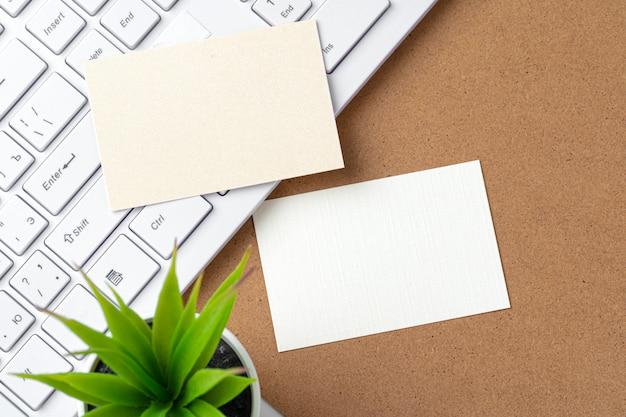 Puste wizytówki z dostawami i klawiaturą na stole w biurze.