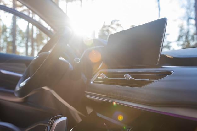 Puste wnętrze auta premium w słońcu.. monitor multimedialny, wewnętrzne owiewki wentylacyjne, kierownica. żadnych ludzi.