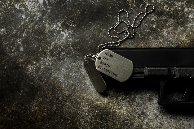 Puste wojskowe nieśmiertelniki i broń na opuszczonym zardzewiałym metalowym talerzu.