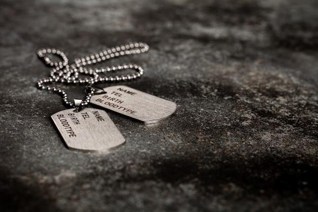 Puste wojskowe nieśmiertelniki na opuszczonym zardzewiałym talerzu metalowym. wspomnienia i ofiary.