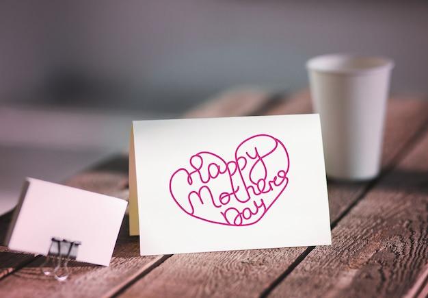 Puste zaproszenie kartkę z życzeniami, aby zastąpić swój projekt na szarym drewnianym stole. koncepcja szczęśliwego dnia matki