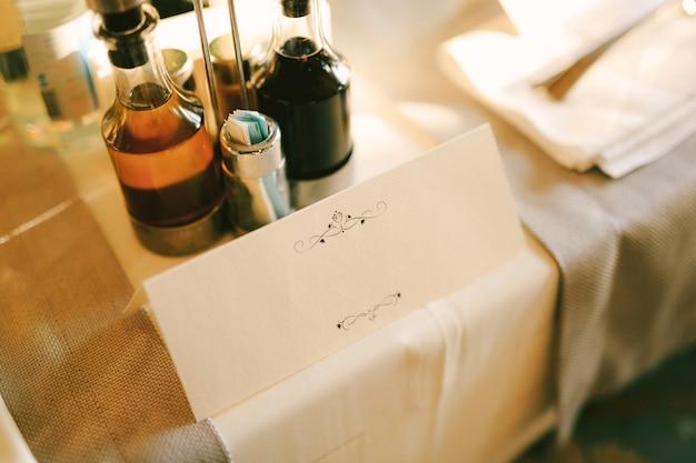 Puste zaproszenie stoi na stole pokrytym białym obrusem i butelkami napojów