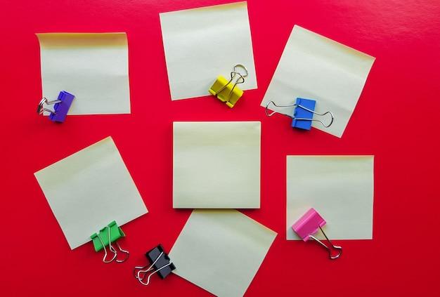Puste żółte karteczki i spinacze do papieru na czerwonym tle, biznes koncepcja pracy. żółte pamiątkowe naklejki na czerwonej ścianie. układ.