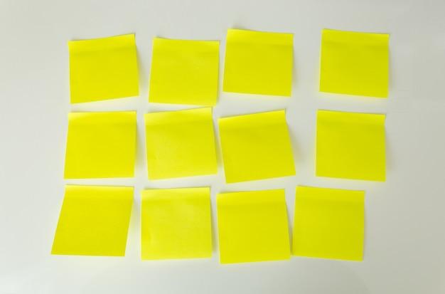 Puste żółte karteczki samoprzylepne na białej tablicy