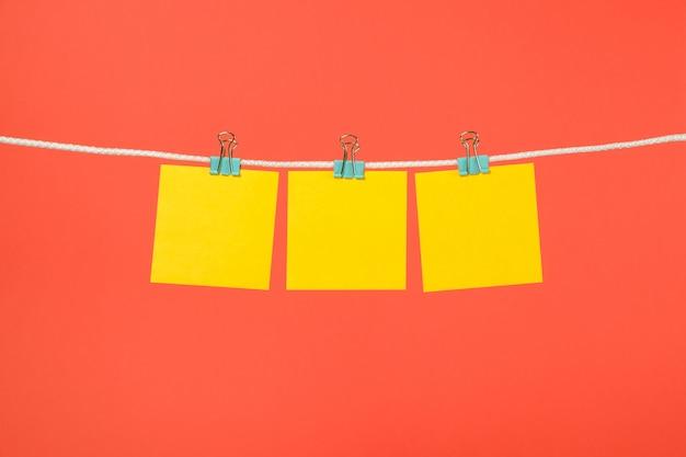 Puste żółte notatki papieru wiszące na sznurku