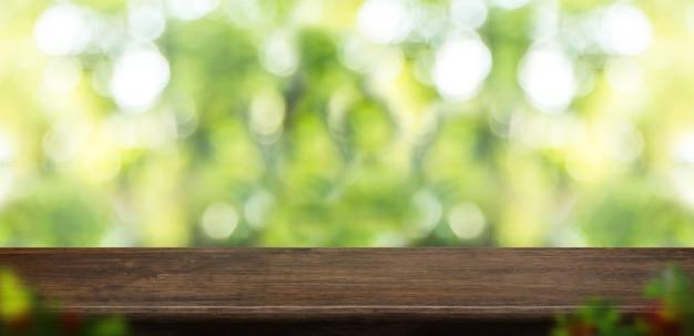 Pustego grunge drewniany stołowy wierzchołek z plamy drzewem w parku z bokeh światłem przy tłem