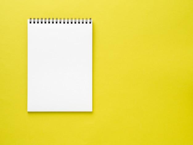 Pustego notatnika biała strona na żółtym biurku, koloru tło. widok z góry, pusty dla tekstu.