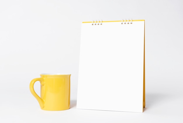 Pustego papieru spirali kalendarz i żółta filiżanka dla makieta szablonu