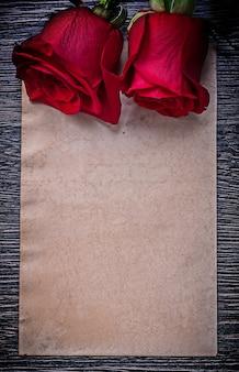 Pustego rocznika papieru czerwone aromatyczne róże na drewnianej desce