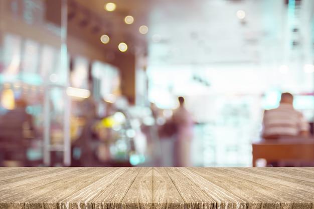 Pustej drewnianej deski stołowy wierzchołek z plama klientem w sklep z kawą z bokeh światłem