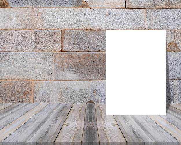 Pusty arkusz na drewnianym stole i oparty o ścianę