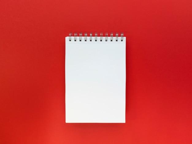 Pusty arkusz notebooka czerwonym tle. koncepcja edukacyjna. mieszkanie leżało z miejscem na kopię.
