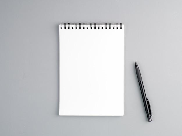 Pusty arkusz notesu spirala i długopis na neutralnym szarym tle z teksturą