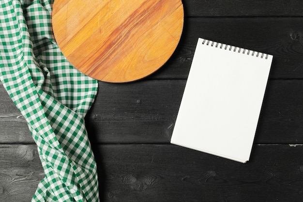 Pusty arkusz otwartego notatnika i naczynia kuchenne na stole z obrusem, miejsce na kopię