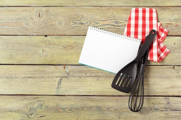 Pusty arkusz otwartego notatnika i przybory kuchenne na stole z obrusem
