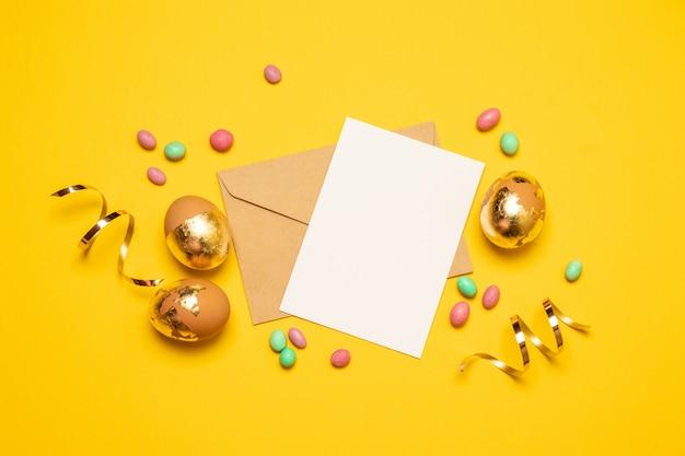 Pusty arkusz papieru i koperta ze złotymi jajkami