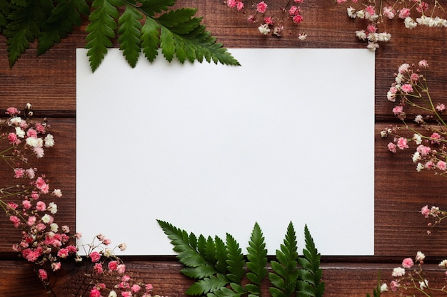 Pusty arkusz papieru i liści paproci z kwiatami na podłoże drewniane